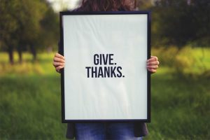 child holding up give thanks sign Thanksgiving is such a fantastic time to share what you are thankful for. This interactive and fun thanksgiving gratitude game involves everyone at the table!