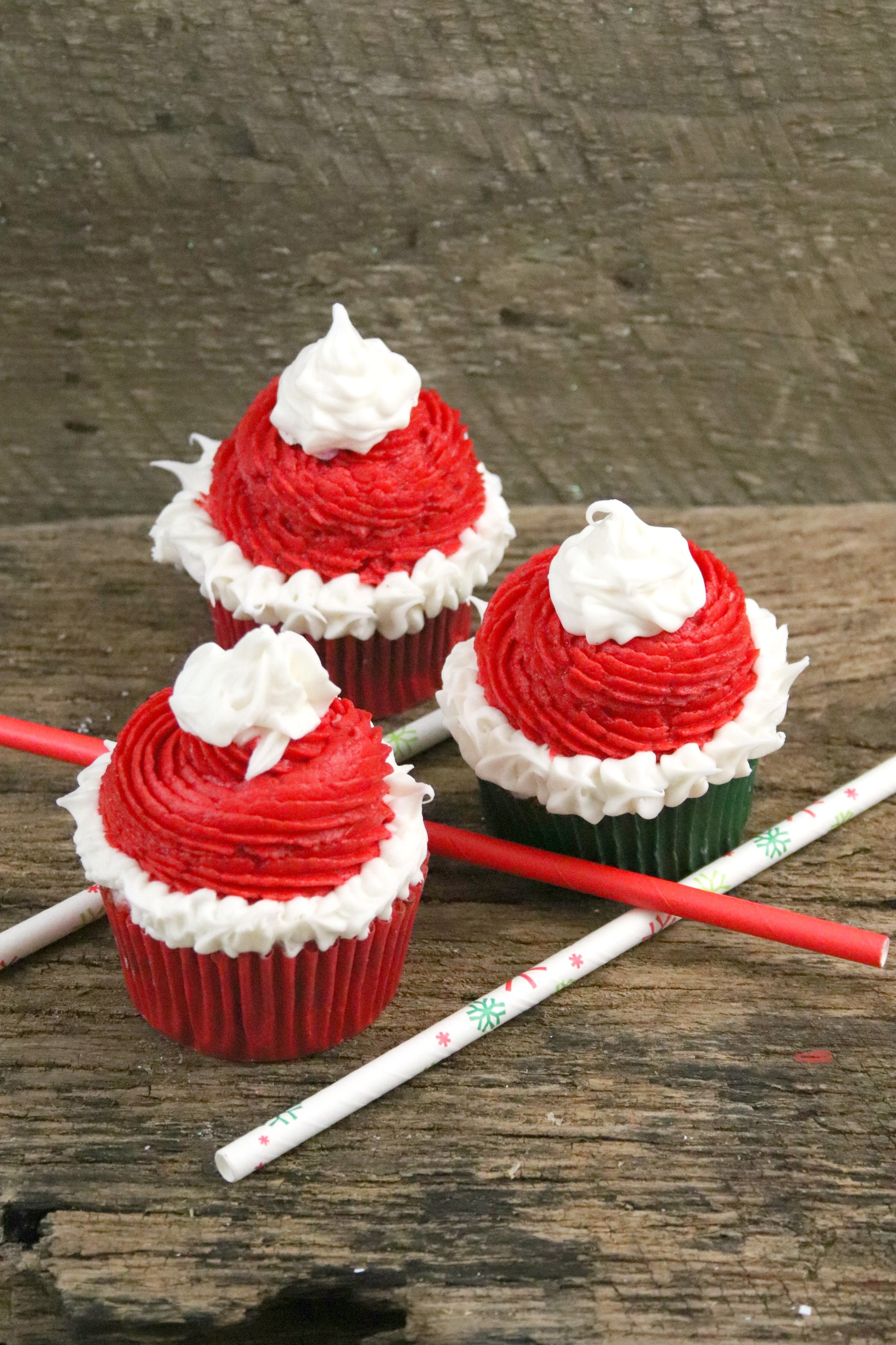 These fun a festive Santa hat Christmas Cupcakes are super fun to make with kids! The recipe features a cocoa buttercream frosting perfect for the season! The red and green inside makes a fun treat for kids! #holidaybaking #christmascupcakes #