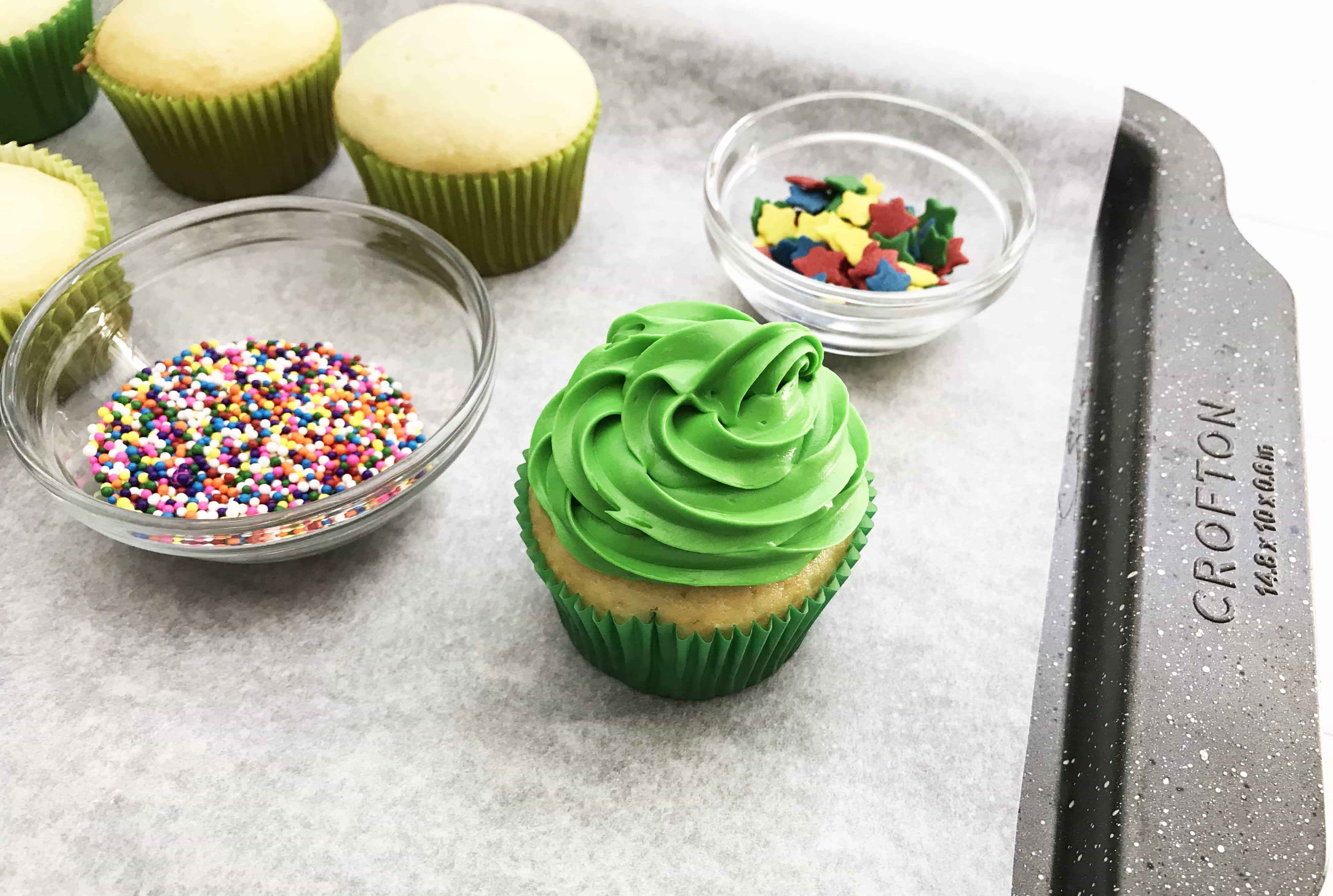 These Christmas Tree Cupcakes are so fun and festive! You can use store bought or your own homemade cupcake recipe for these delicious treats! They are perfect for holiday parties, bake sales and so much more. The pretty green color makes it super attractive to anyone!