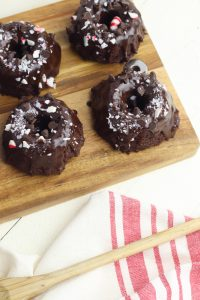 These chocolate peppermint mini bundt cakes are super easy to make! The easy recipe uses a combination of cake mix and frosting and crushed peppermint on top. This is a great recipe to make with kids! #baking #holidayrecipes #peppermint
