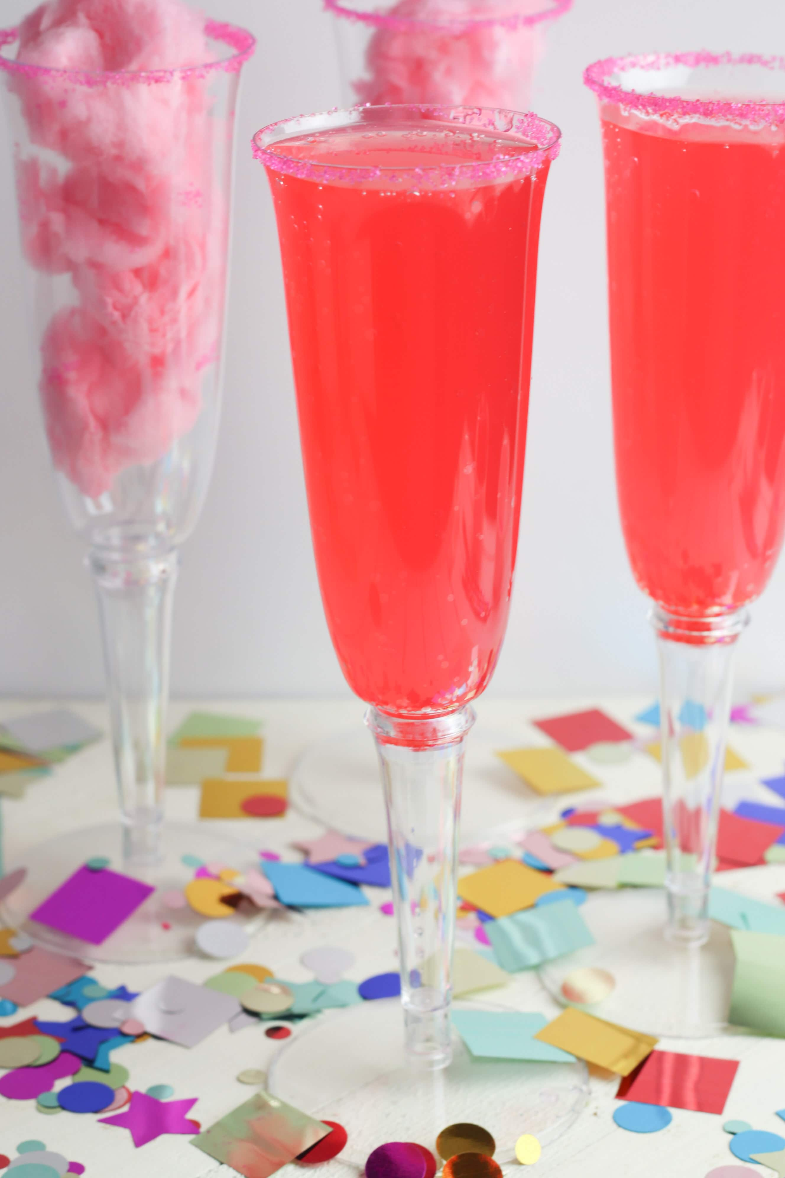 This fun and sweet non alcoholic tasty cotton candy mocktail has a very beautiful and festive pink color! This is a super fun drink to make for kids or non drinkers at a party! The recipe calls for cotton candy, pink sugar and strawberry soda which makes for a pretty sparking pink drink. This is a great sparkling drink recipe for a crowd! Your guests will be so impressed! #mocktail #nonalcoholicdrinks #nonalcoholic #mocktailrecipe