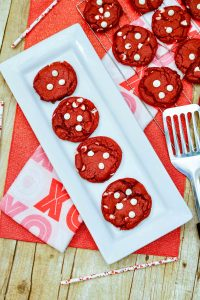 Here is a fun recipe for White Chocolate Chip Valentine's Day Cookies that you can bake for the sweethearts in your life! They are super festive and fun with a bright red color. Made super quick with red velvet cake mix and white chocolate chips, it's a super fun treat to make with the kids or for your love! #valentinesday #valentinesdaycookies #valentinesdaysweets