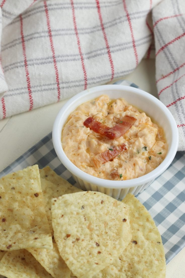 Here is a super easy and delicious bacon cheddar dip that is a sure crowd pleaser! This dip is made on the stove, served warm with chips or crackers. Three easy main ingredients include cream cheese, bacon and cheddar cheese. #appetizers #dips #cheesedip