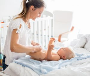 mom putting diapers on baby